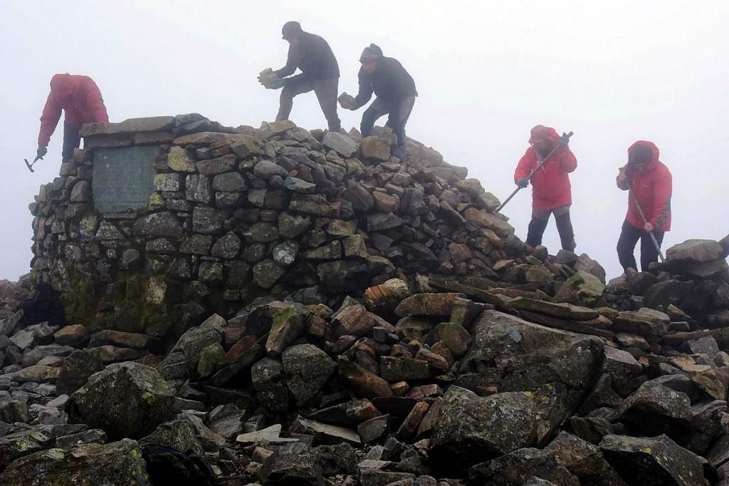 Rangers work on restoring the summit cairn. Photo: Paul Kinston/NNP