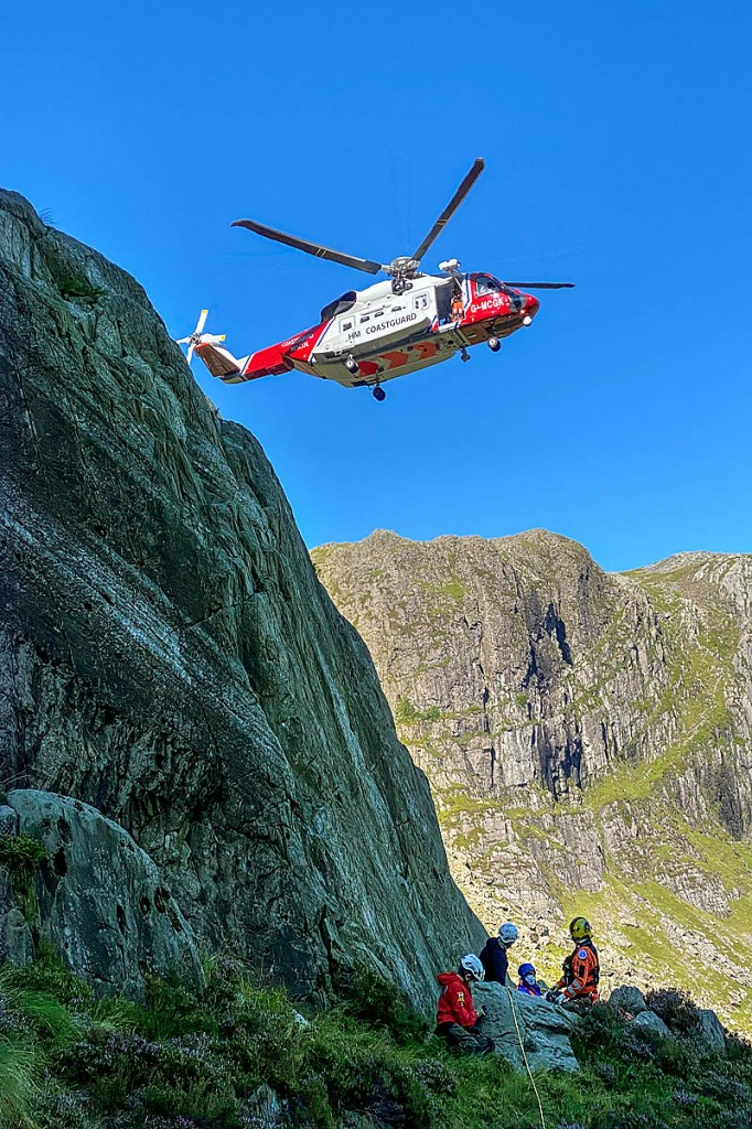 Rescuers and the Coastguard helicopter at the rescue site on Glyder Fawr. Photo: OVMRO