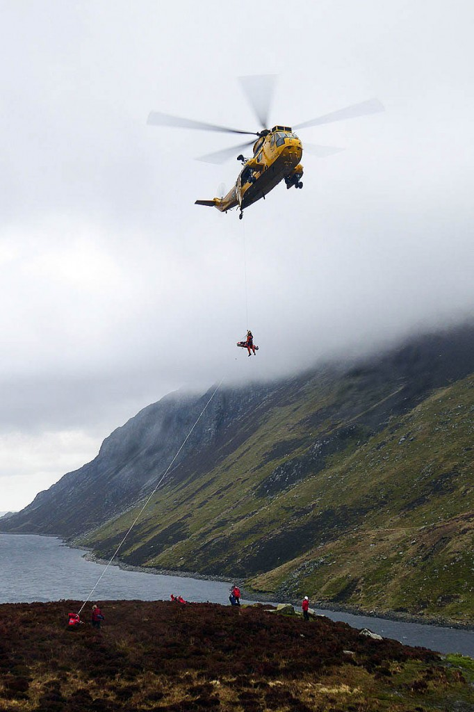 The injured woman is winched into the RAF Valley Sea King at Llyn Cowlyd as Ogwen Valley team members operate a high line from the ground. Photo: OVMRO