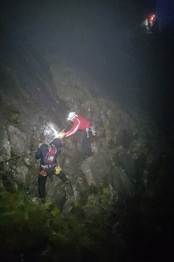 Rescuers help one of the walkers to safety. Photo: Karl Lester/OVMRO