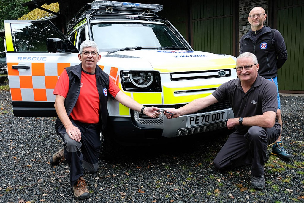 Mike Childs, left, receives the vehicle keys from Colin Todd of Lakeland Land Rover, with Mike Rippon, right. Photo: Patterdale MRT
