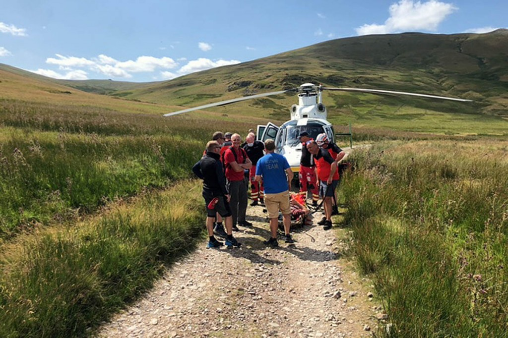 Rescuers with the air ambulance, which landed on the Old Coach Road. Photo: Patterdale MRT