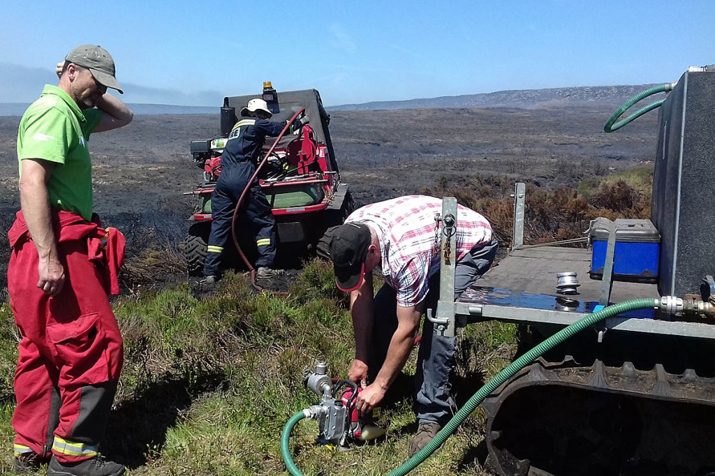 National park staff replenish the water tank on a firefighters' all-terrain vehicle. Photo: Dave Watts