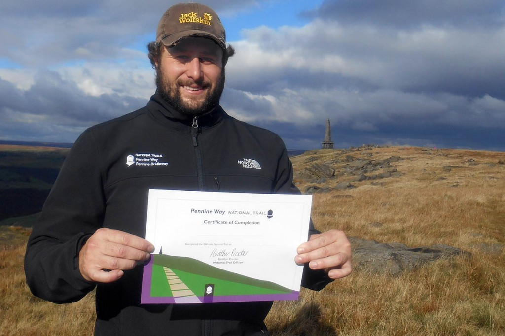 Yorkshire Dales National Park Authority Pennine Way ranger Colin Chick with one of the certificates, on the approach to Stoodley Pike. Photo: Pennine National Trails Partnership