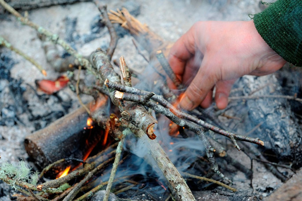 Campfires should be kept under control. Photo: Lorne Gill/SNH Putting dry twigs on an open fire.