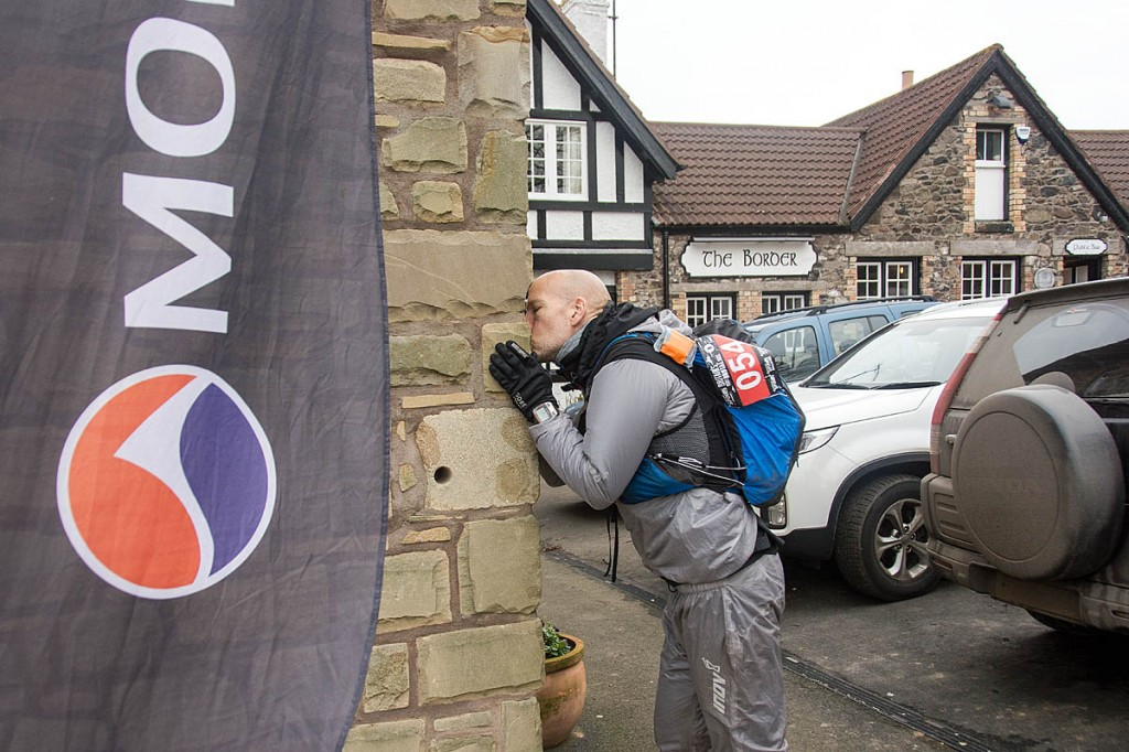 Tom Hollins kisses the wall of the Border Hotel at end of the Spine Race. Photo: Mick Kenyon/Montane Spine Race