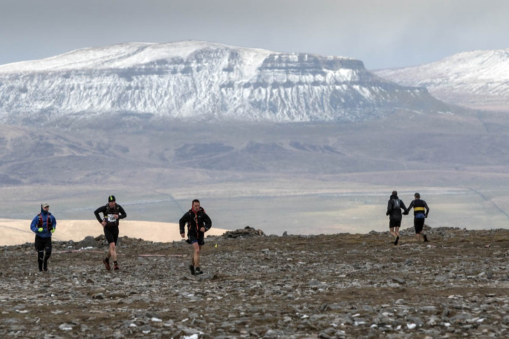 Runners on the summit plateau of Ingleborough, with Pen-y-ghent in the distance