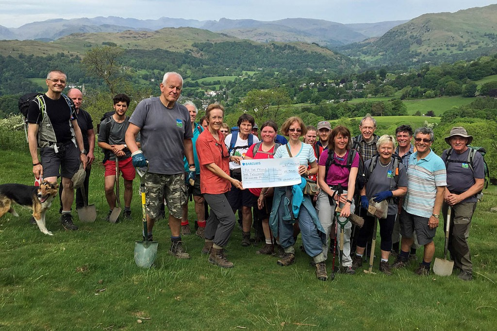 Caroline Nichol, right, organiser of the charity challenge, presents the £1,500 cheque to Fix the Fells programme manager Joanne Backshall, left, with members of the Wainwright Society and volunteers from Fix the Fells. Photo: Tim Backshall