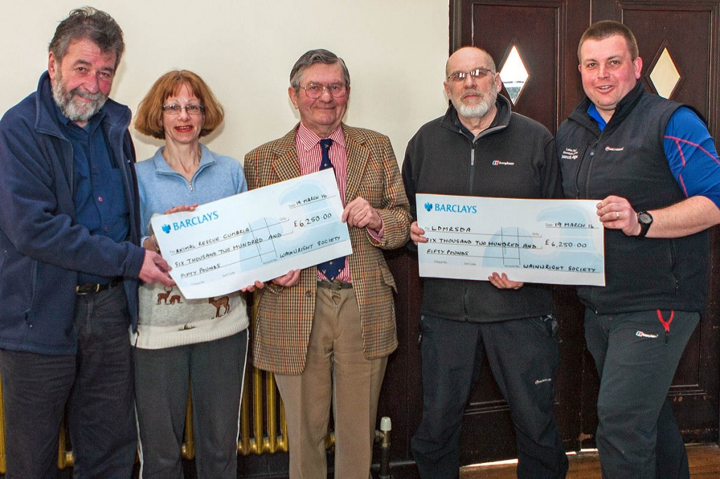 Wainwright Society chairman Eric Robson, left, hands out cheques to, from left: Caroline Nichol and John Estensen ofAnimal Rescue Cumbria; Nick Holmes and John Leadbetter of Lake District Mountain Rescue Search Dogs. Photo: Andrew Stainthorpe