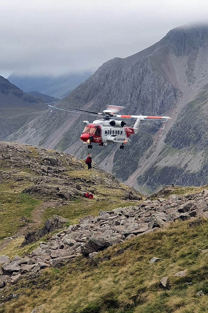 Team members are winched from the Caernarfon helicopter onto Scafell Pike before making their way to the summit. Photo: Wasdale MRT