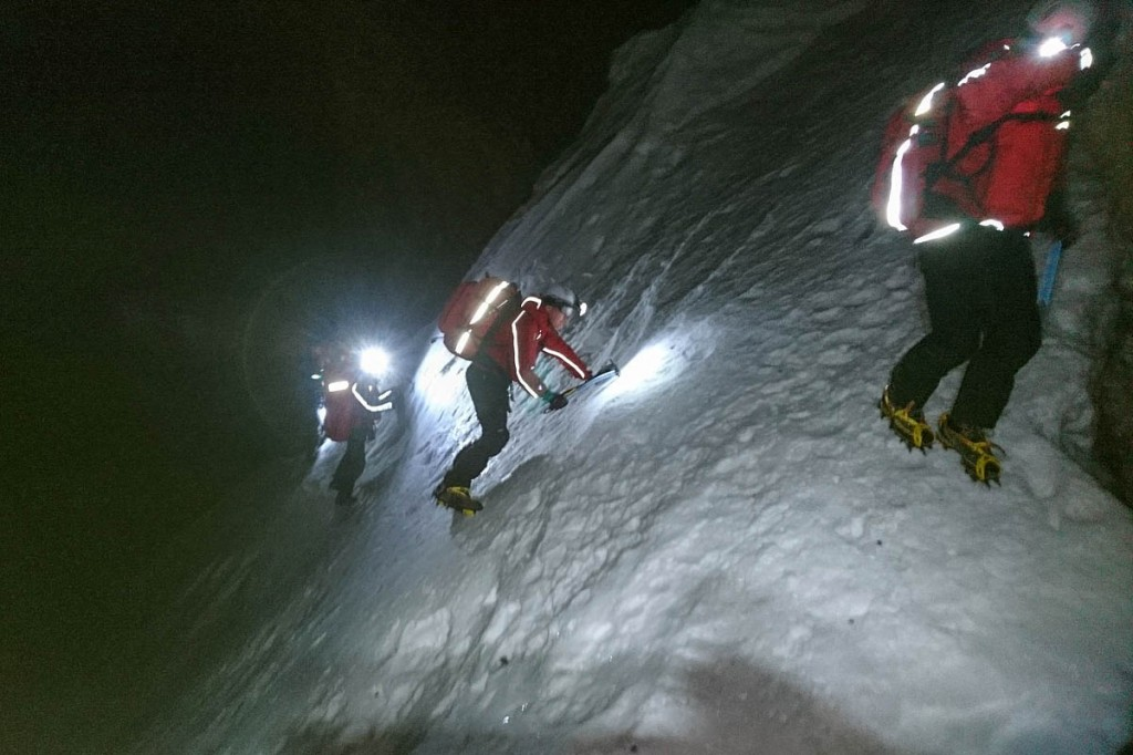 Rescuers use ice-axes and crampons on the steep snow slope. Photo: Pete Baines/Wasdale MRT