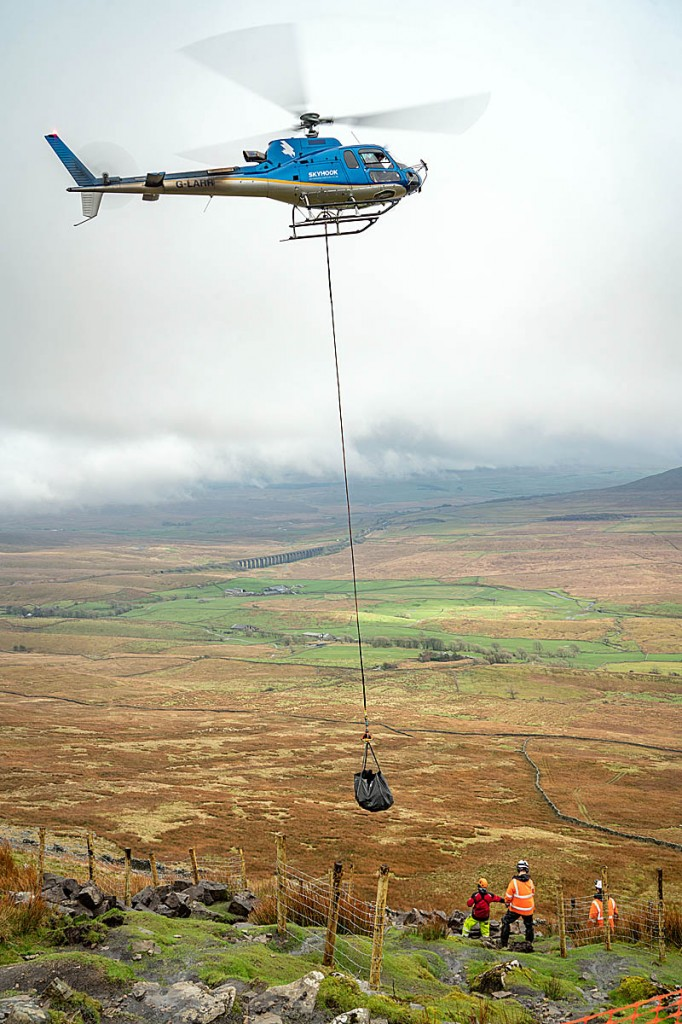The helicopter lifts a load of stone on to the flanks of Whernside. Photo: Andy Kay/YDNPA
