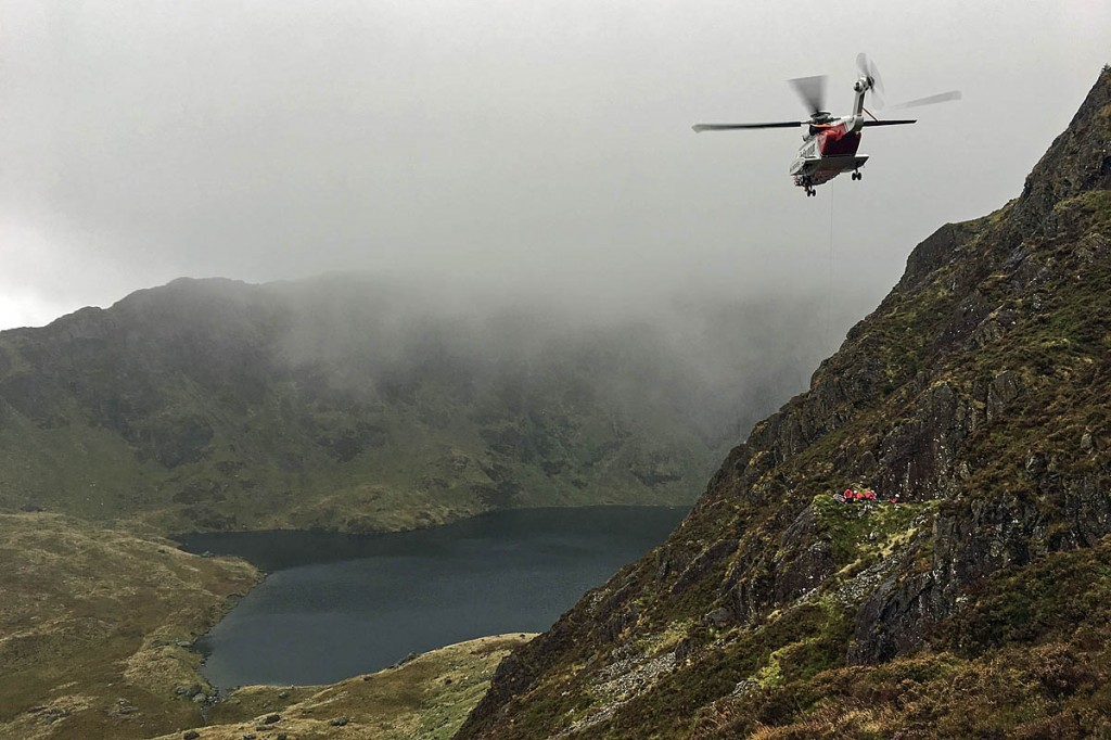 Rescue team members and the Coastguard helicopter at the site above Llyn Cau on Cadair Idris. Photo: Aberdyfi SRT