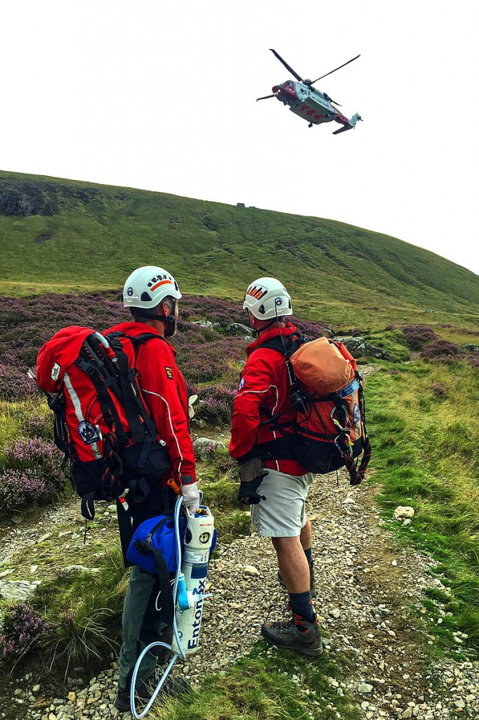 Team volunteers look on as the casualty is airlifted from the mountain. Photo: Aberdyfi SRT