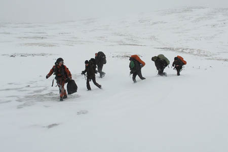 Petty Officer Mike Henson leads five of the walkers to the safety of the Royal Navy helicopter