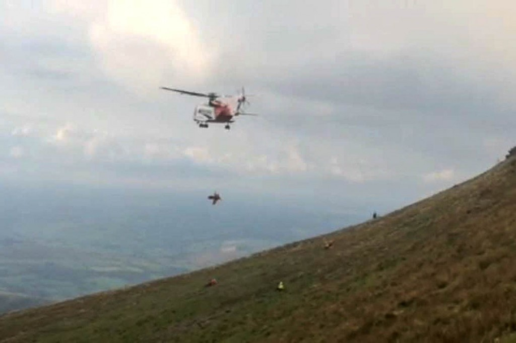 The injured man is winched into the helicopter from the slopes of Corn Du. Photo: Brecon MRT