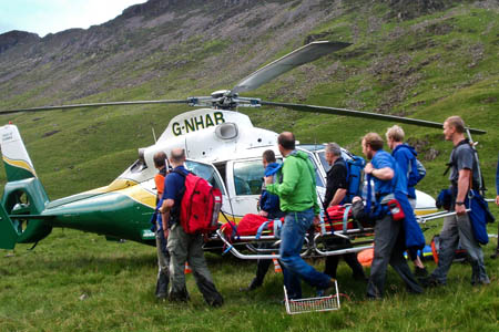 Cockermouth Mountain Rescue Team members carry the walker to the helicopter. Photo: Cockermouth MRT