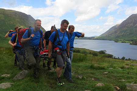Team members stretcher the injured woman to Buttermere. Photo: Cockermouth MRT
