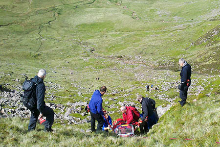 Rescuers stretcher the man down the hillside. Photo: Cockermouth MRT