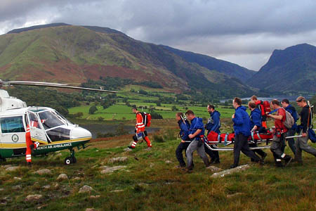 Rescuers carry the walker to the helicopter. Photo: Cockermouth MRT