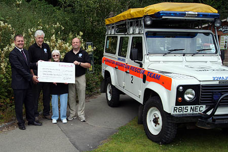 Ian Quayle presents a cheque to Coniston MRT members Anthony 'Rob Robinson, team Leader; Carol Carroll and Jeff Carroll, treasurer