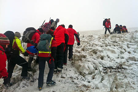 Mountain rescue team members stretcher the injured walker from Corn Du