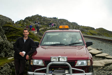 Craig Williams stands beside the maroon Frontera on Snowdon
