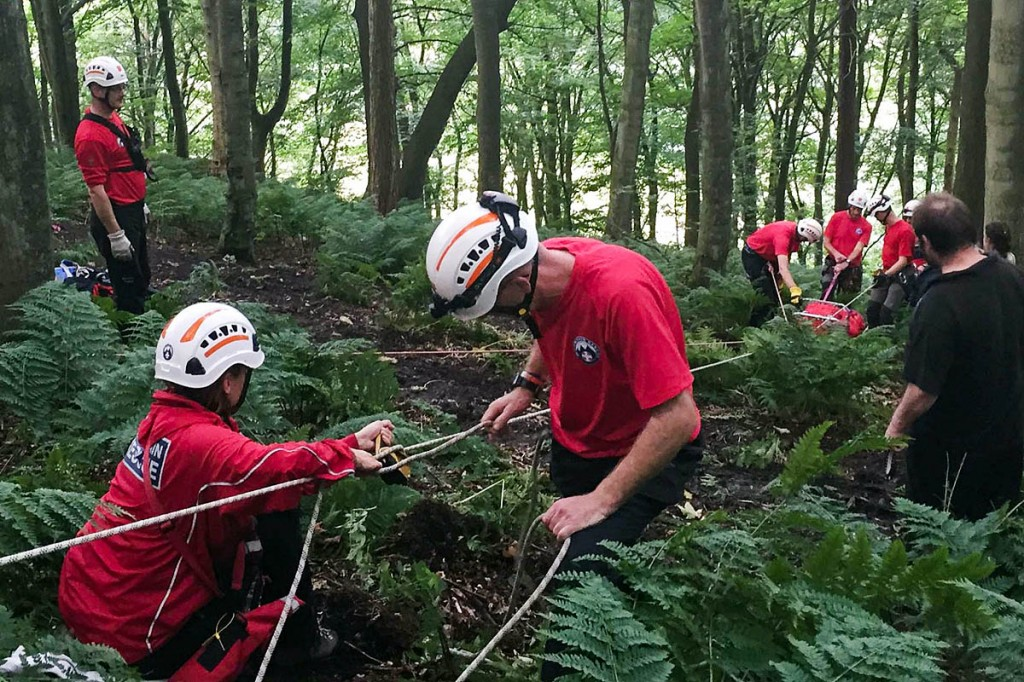 Team members lower the woman in a stretcher, using a rope system. Photo: Calder Valley SRT