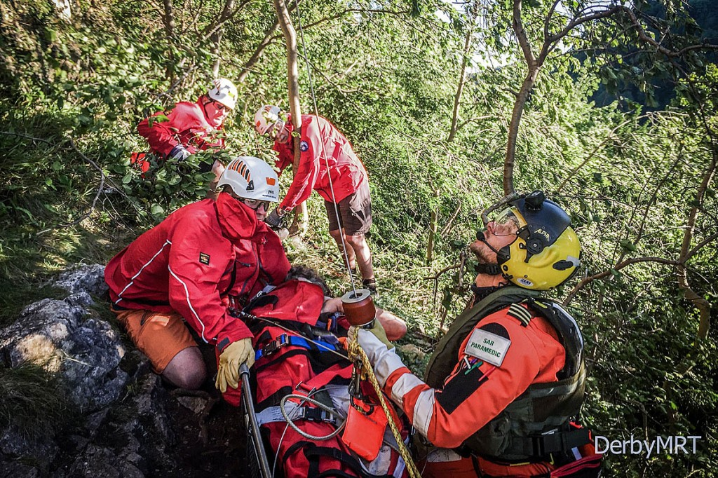 Rescue team members and Coastguard crew prepare to winch the injured man. Photo: Derby MRT