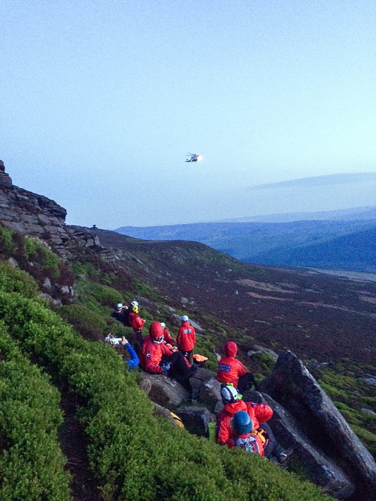 The helicopter approaches as Edale team members treat the injured climber on Dovestone Tor. Photo: Edale MRT