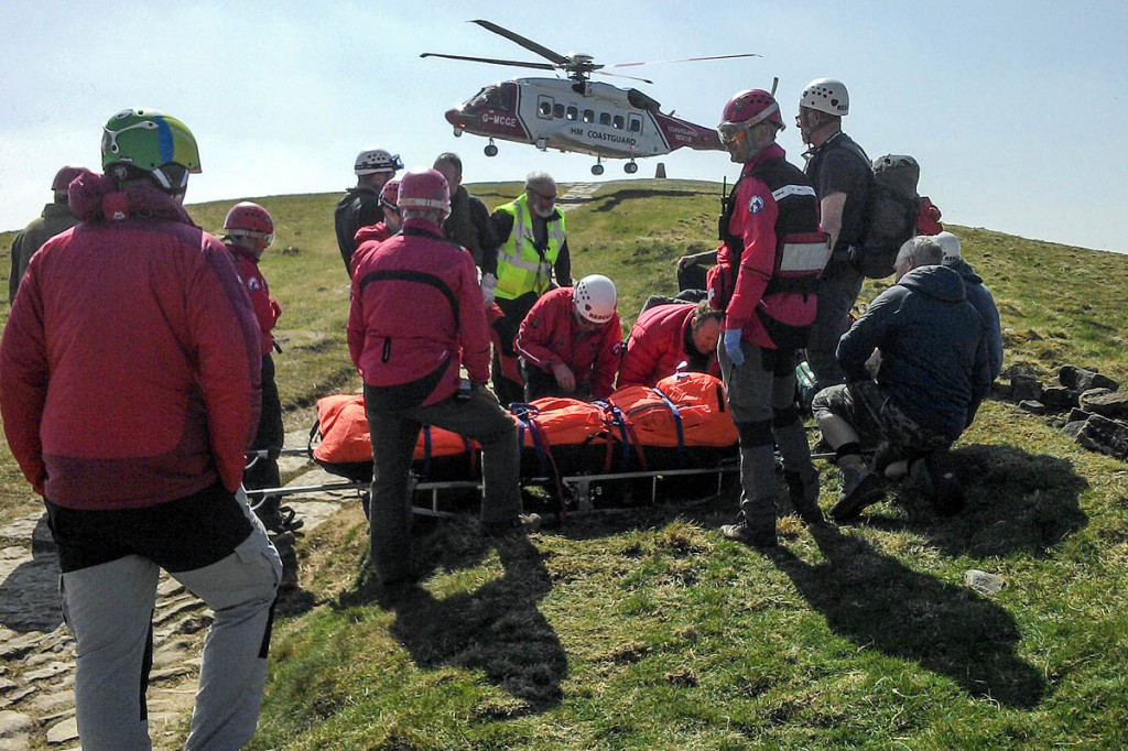 Rescuers with the injured paraglider and the Coastguard Sikorsky on Mam Tor. Photo: Edale MRT