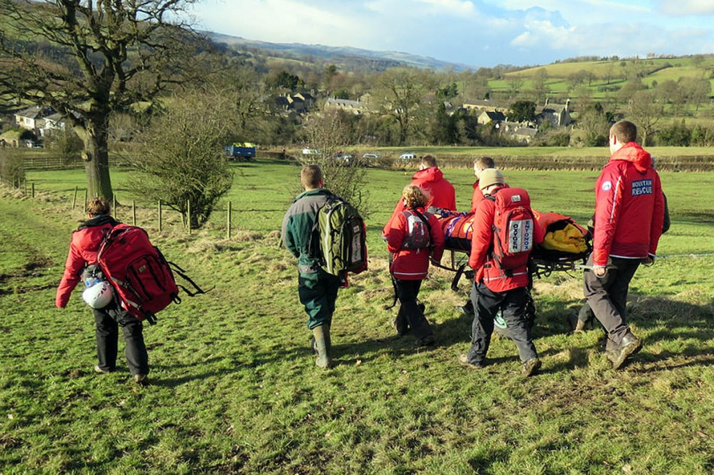 Rescuers stretcher the injured walker from the hillside. Photo: Edale MRT