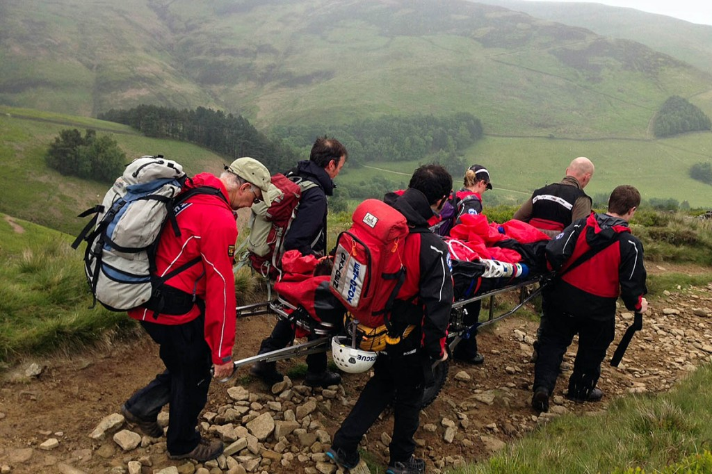 Rescuers stretcher the runner from the hill. Photo: Edale MRT