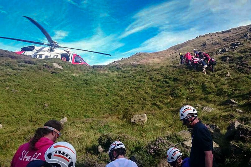Rescuers stretchered the injured walkers up a steep slope to the helicopter. Photo: Edale MRT