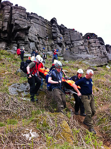 Edale Mountain Rescue Team members strecher the climber from Stanage. Photo: Edale MRT
