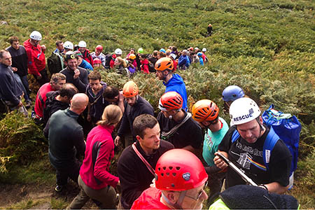 Fellow climbers line up to help get one of the injured pair from the crag. Photo: Edale MRT