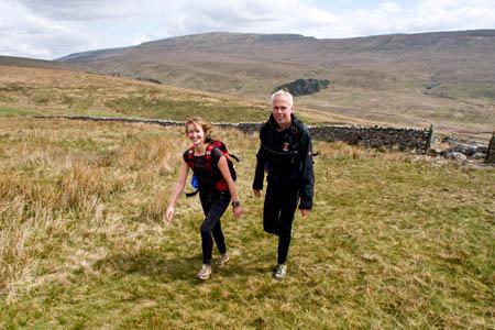 Two Fellsman competitors climb Gragareth, with Whernside behind them
