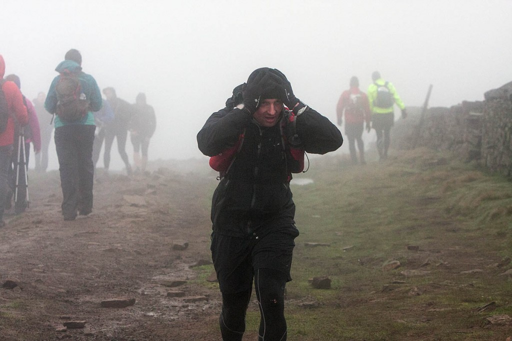Hang on to your hat: a Fellsman competitor arrives at the Whernside summit