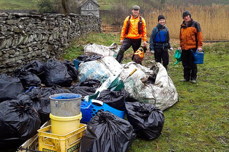 Volunteers with some of the rubbish, including watering cans