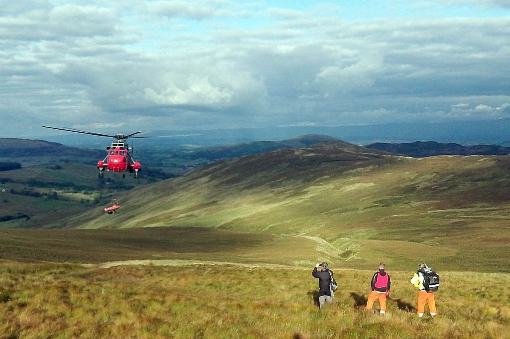 The walker is winched into the Royal Navy helicopter as air ambulance crew look on. Photo: GNAAS
