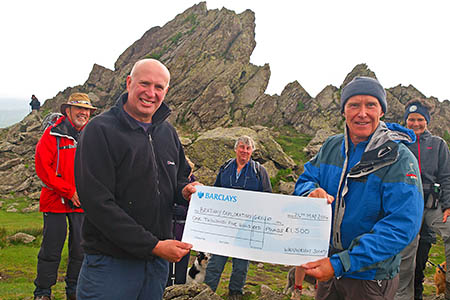 Alan Hinkes presents a £1,500 cheque to the Brathay Exploration Group on top of Helm Crag. Photo: Derek Cockell