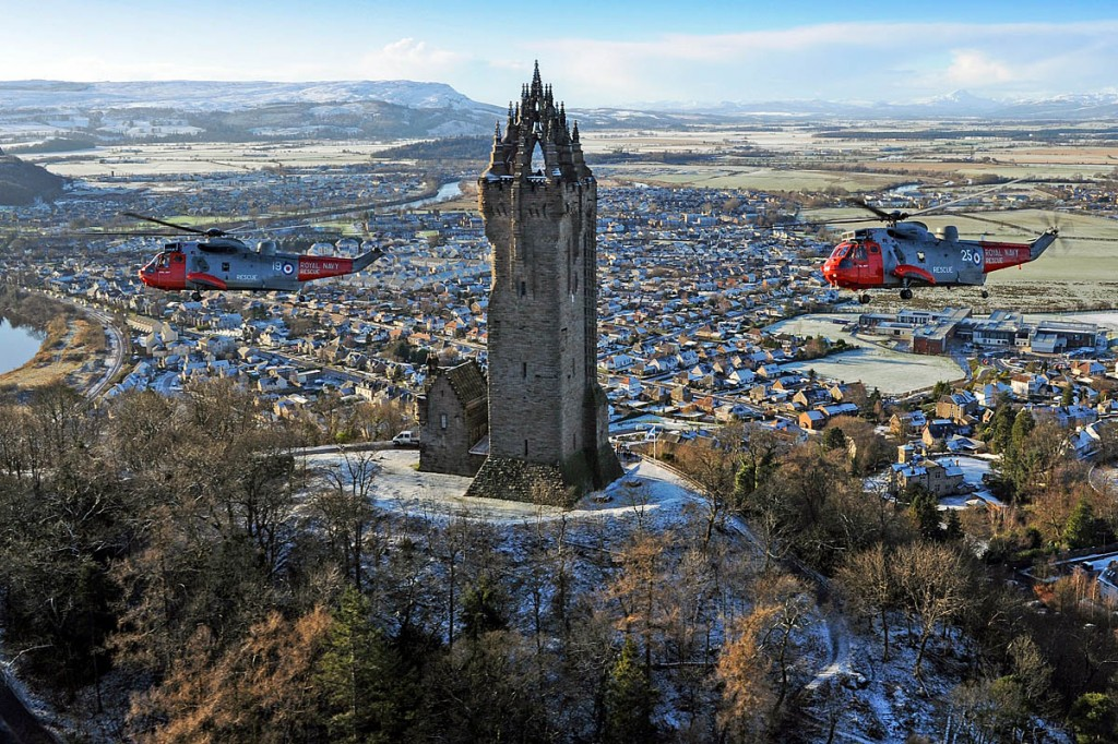 The HMS Gannet Sea Kings pass over the Wallace Monument at Stirling during the fly-past. Photo: Thomas McDonald/Royal Navy