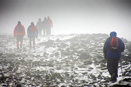 Walkers in poor visibiltiy in winter on Ingleborough's summit
