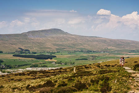 Walkers ascend Ingleborough from Chapel-le-Dale, with Whernside in the background
