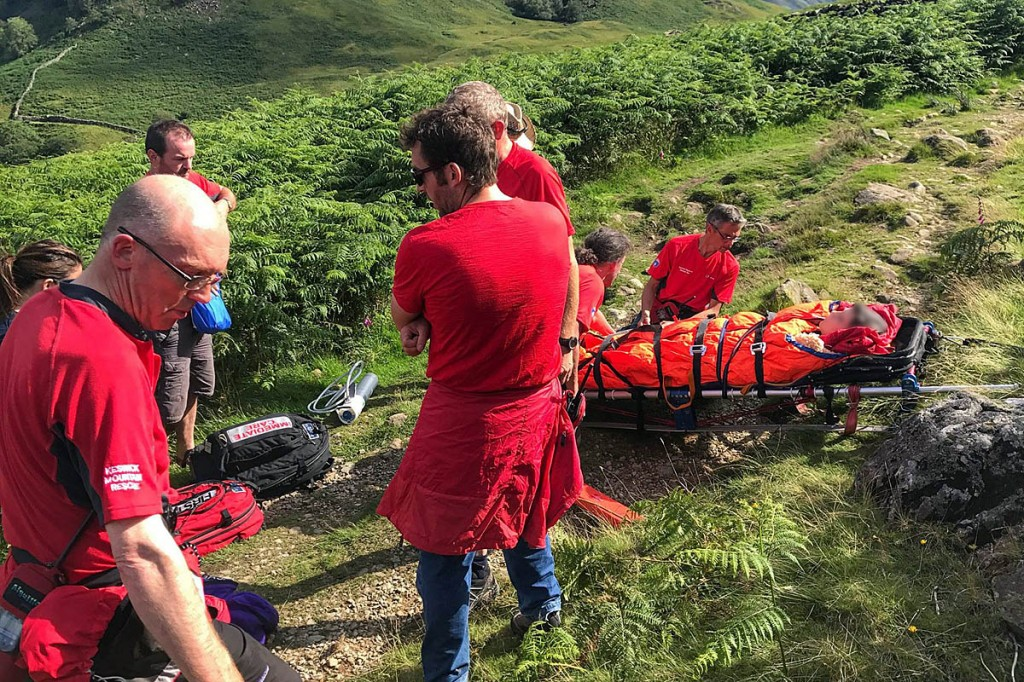 Rescuers with the injured woman on the fell. Photo: Keswick MRT