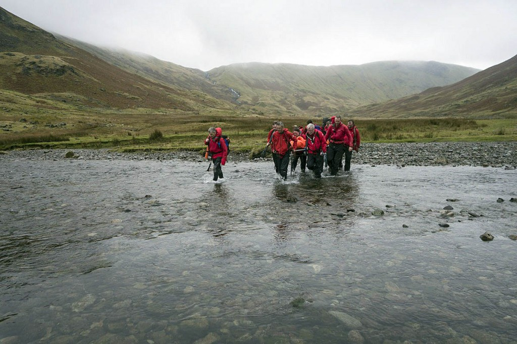 Rescuers stretcher the injured runner across Langstrath Beck. Photo: Keswick MRT