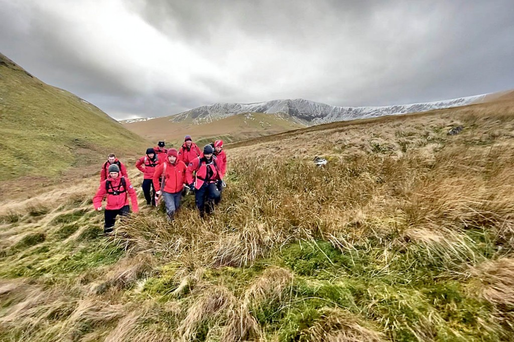 Rescuers stretcher the injured walker from the fell. Photo: Keswick MRT