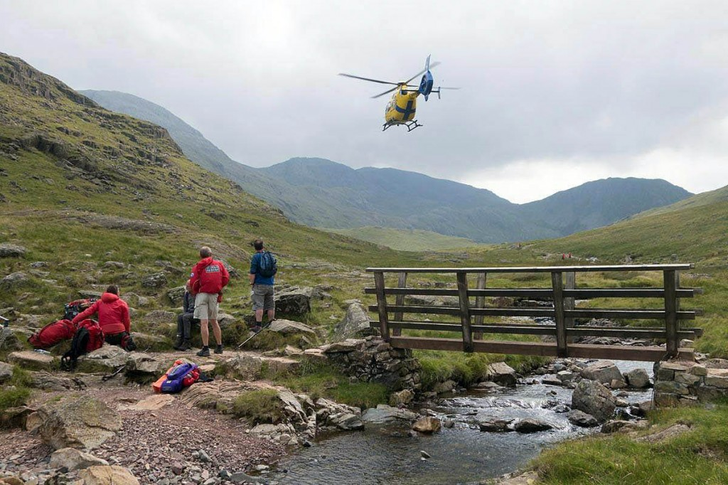 Team members and the North West Air Ambulance at the rescue site. Photo: Keswick MRT