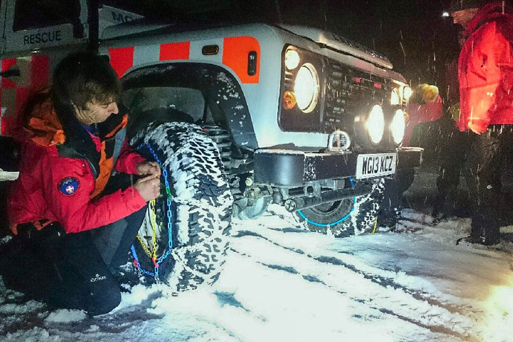 The team fits snow chains to its Land Rover for the rescue. Photo: Keswick MRT