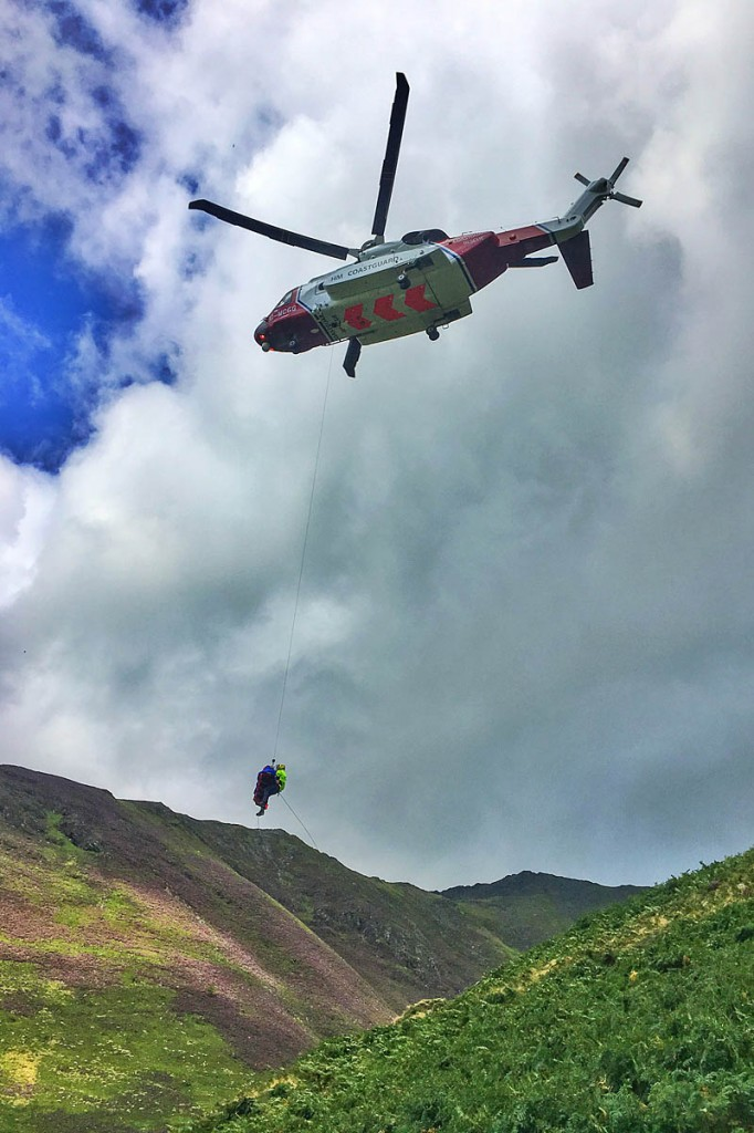 The injured man is winched into the Coastguard helicopter. Photo: Keswick MRT